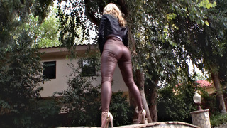 Ashley Fires posing in a tight leather pants and high heels